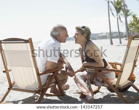Romantic senior couple sitting on deckchairs at tropical beach - stock photo