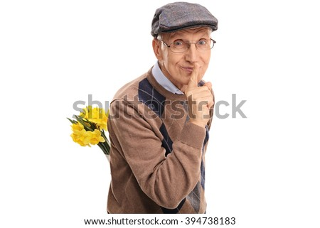 Romantic senior holding a bunch of flowers behind his back and gesturing silence isolated on white background - stock photo