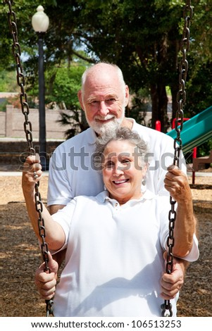 Romantic senior husband pushing his lovely wife in a swing on a playground. - stock photo