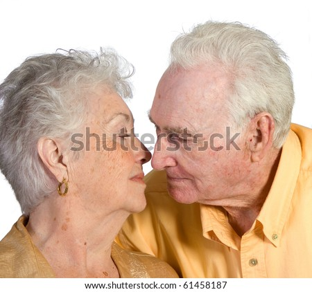 Romantic senior man and woman showing affection. Shot against white background. - stock photo