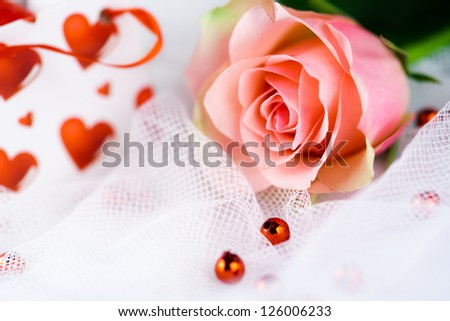 Romantic single perfect pink rose nestling on gauze for a loving sweetheart, Valentine, wedding or anniversary greeting card - stock photo