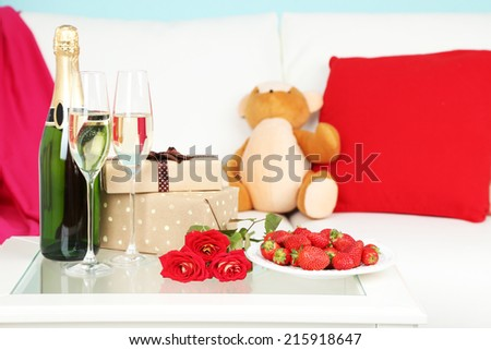 Romantic still life with champagne, strawberry and roses in room - stock photo