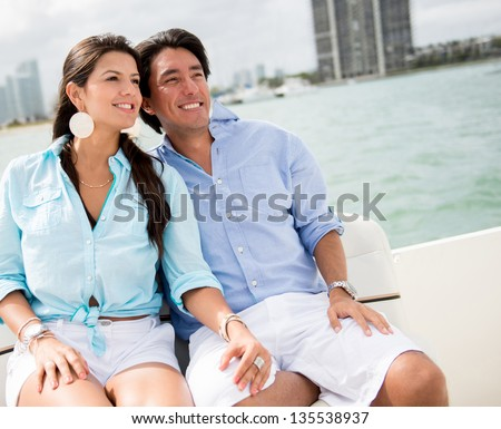 Romantic summer couple in a boat looking very happy - stock photo