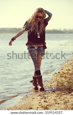 Romantic summer girl in boho style clothes walking along the riverside. Boho, hippie. - stock photo
