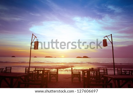 romantic sunset and beach restaurant silhouette - stock photo