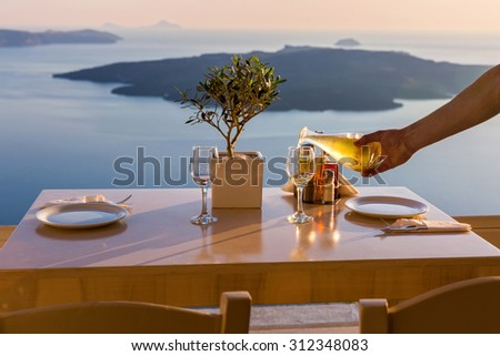 Romantic table for two on the island Santorini, Greece. Views of the sea and the volcano - stock photo