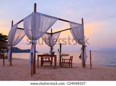 Romantic table setting on the beach at sunset - stock photo
