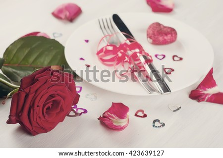 Romantic table setting with roses plates and cutlery .Toned photo - stock photo