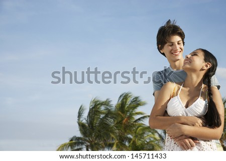Romantic teenage couple embracing on tropical beach - stock photo