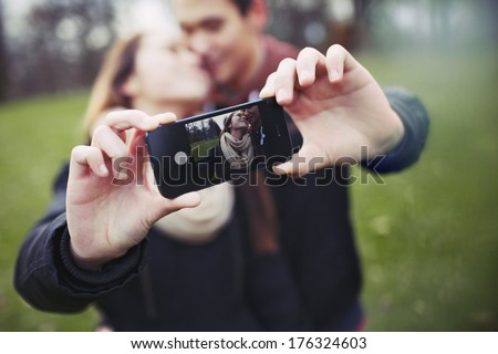 Romantic teenage couple taking self portrait with cell phone at the park. Young man and woman in love. Asian male and female model. - stock photo