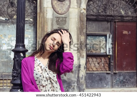 Romantic trendy woman with black hair with closed eyes dreaming on the old city street. Fashionable woman in bright pink jacket and chiffon blouse with a bow, street fashion look, summer outfit. - stock photo
