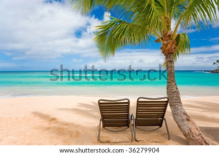 romantic tropical beach with palm tree and two chairs on sand - stock photo