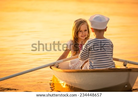 Romantic walk around the lake on a boat sailor boy and girl - stock photo