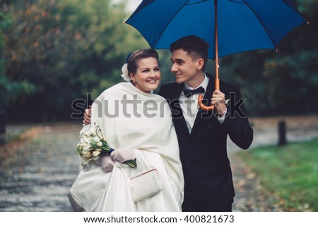 Romantic walking of newlyweds. The groom and bride are walking under umbrella in the park. Couple are smiling, they are happy. Newlyweds in love. They became husband and wife this day. - stock photo