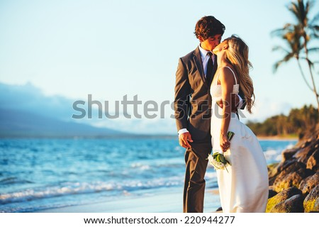 Romantic Wedding Couple Kissing on the Beach at Sunset - stock photo
