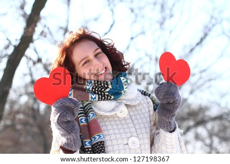 Romantic winter girl with two red hearts - stock photo
