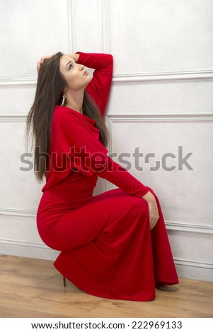 Romantic woman dressed in red sitting near wall - stock photo