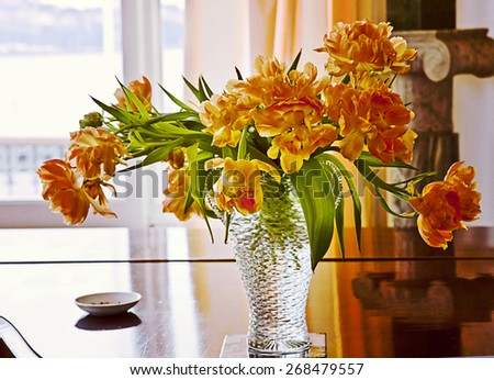 Romantic yellow orange tulips in glass in a room interior - stock photo