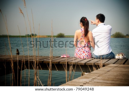 Romantic young asian couple in love sitting on pier. - stock photo