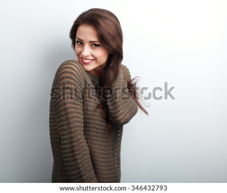 Romantic young beautiful woman holding hair in warm sweater on blue background - stock photo