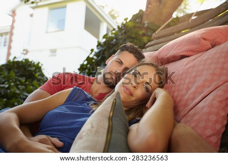 Romantic young caucasian couple relaxing on a hammock together and looking at camera. Young man and woman on garden hammock in their backyard. - stock photo