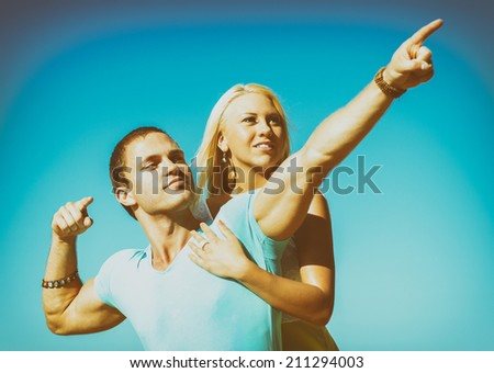Romantic young couple against blue sky. - stock photo