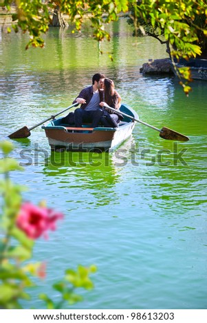 Romantic young couple boating on calm lake. - stock photo