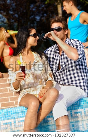 Romantic young couple by swimming pool having drinks, smiling. - stock photo