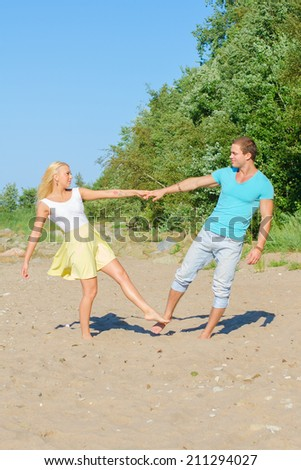 Romantic young couple dancing on the beach. - stock photo