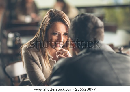 Romantic young couple dating and flirting at the bar, staring at each other's eyes - stock photo