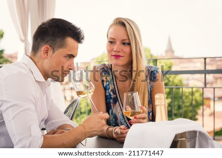 Romantic young couple drinking a glass of wine in a hotel terrace.  - stock photo