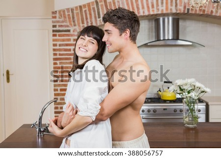 Romantic young couple embracing each other in kitchen - stock photo