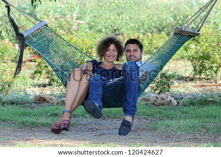 Romantic young couple enjoying a hammock in the park - stock photo