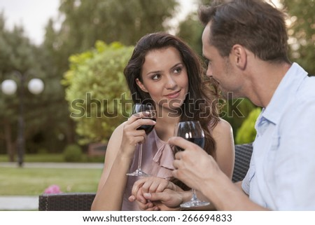 Romantic young couple holding hands while having red wine in park - stock photo
