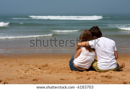 Romantic young couple in casual clothes sitting on the sandy beach and looking to ocean - stock photo