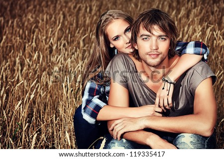 Romantic young couple in casual clothes sitting together in a wheat field. - stock photo