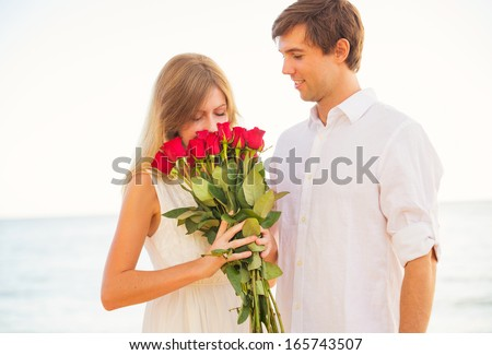 Romantic Young Couple in Love, Man giving beautiful young woman red roses - stock photo