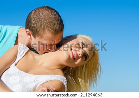 Romantic young couple kissing against blue sky. - stock photo