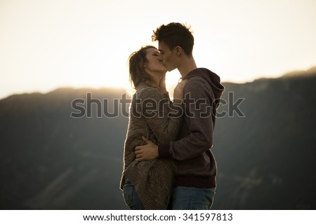 Romantic young couple kissing passionately at sunset, mountains on background, feelings and relationships concept - stock photo