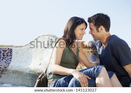 Romantic young couple looking at each other while sitting together on stone bench at Barcelona - stock photo