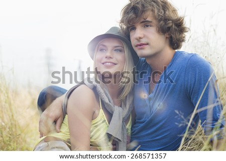 Romantic young couple looking away while sitting in field - stock photo
