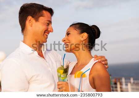 romantic young couple on cruise having cocktails - stock photo