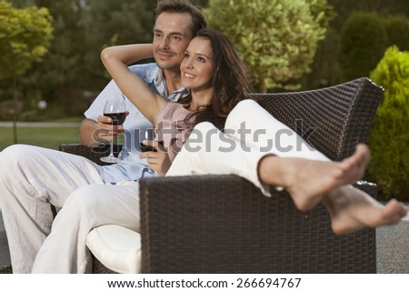 Romantic young couple on easy chair looking away in park - stock photo