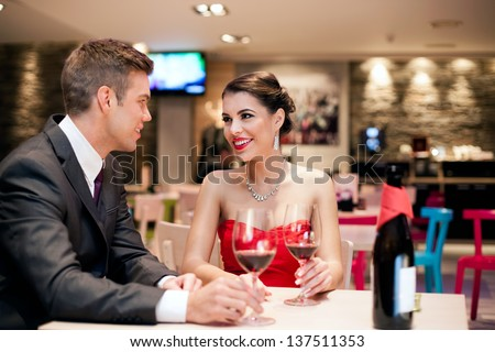 romantic young couple on first date in restaurant - stock photo