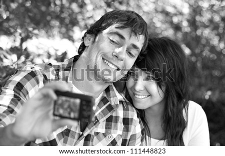Romantic young couple posing for a self portrait with small pocket camera in hand - stock photo