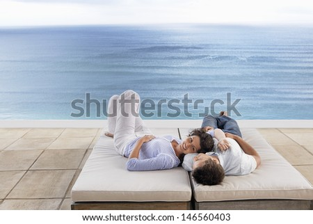 Romantic young couple relaxing on sunbeds by infinity pool at resort - stock photo
