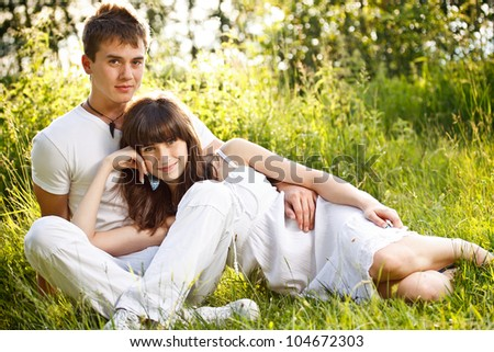 Romantic young couple relaxing outdoors in park smiling - stock photo