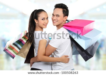 Romantic young couple shopping in the mall with many shopping bags - stock photo