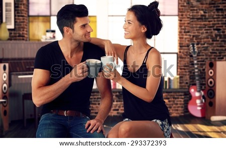 Romantic young couple sitting at home, drinking tea, smiling. - stock photo