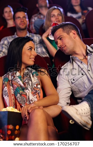Romantic young couple sitting at movie theater, looking each other with love. - stock photo